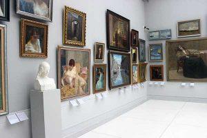 Bilder und Büste in einer Ausstellung.